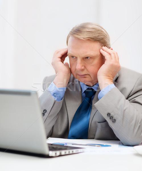 upset older businessman with laptop in office Stock photo © dolgachov