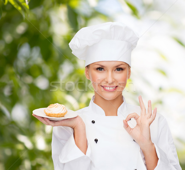 smiling female chef with cake on plate Stock photo © dolgachov