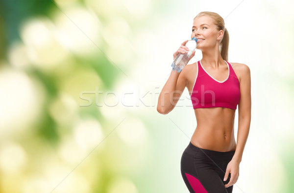 Stock photo: smiling woman with bottle of water