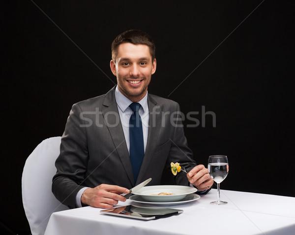 Glimlachend man eten hoofdgerecht restaurant Stockfoto © dolgachov