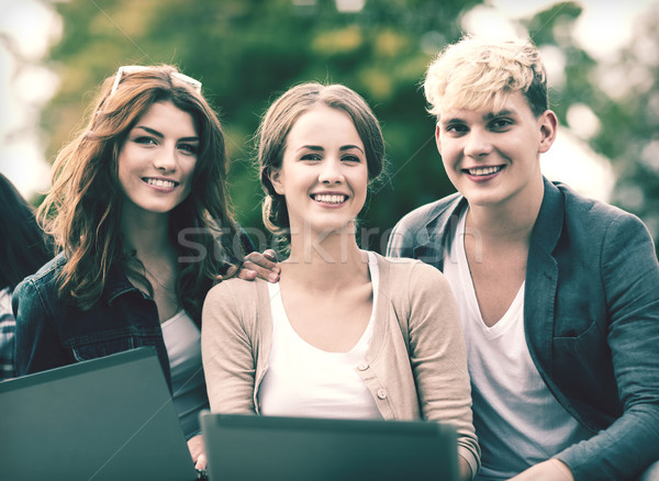 students or teenagers with laptop computers Stock photo © dolgachov