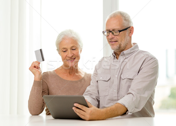 Stock photo: happy senior couple with tablet pc and credit card