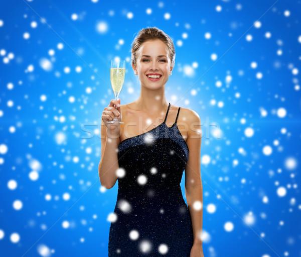 smiling woman holding glass of sparkling wine Stock photo © dolgachov