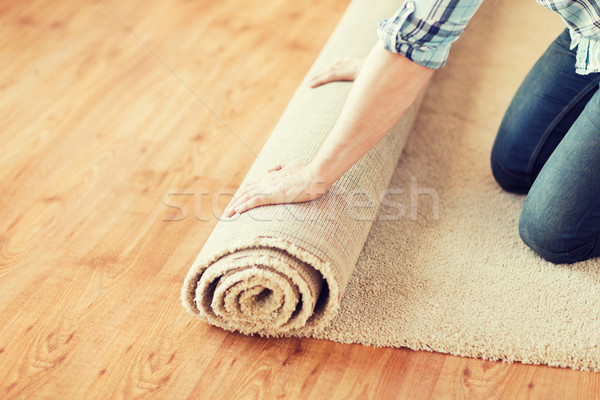 close up of male hands unrolling carpet Stock photo © dolgachov