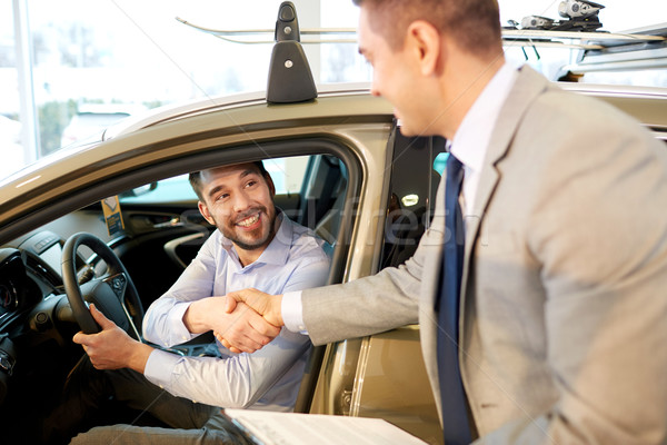 happy man with car dealer in auto show or salon Stock photo © dolgachov