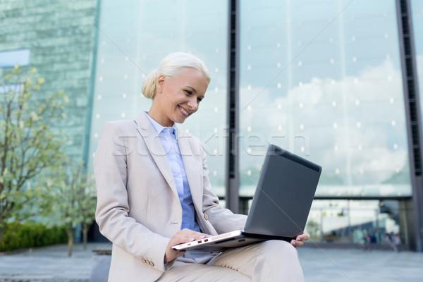 Mosolyog üzletasszony dolgozik laptop kint üzlet Stock fotó © dolgachov