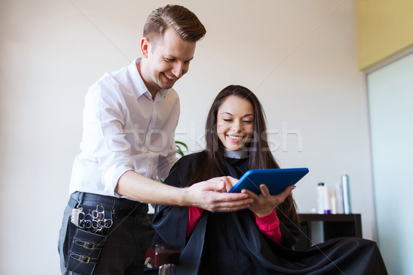 happy woman and stylist with tablet pc at salon Stock photo © dolgachov