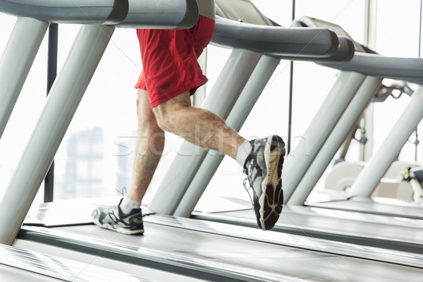 close up of male legs running on treadmill in gym Stock photo © dolgachov