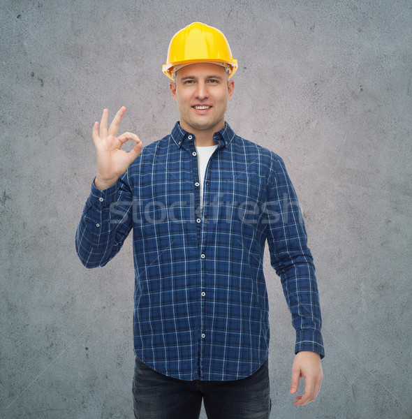 smiling male builder in helmet showing ok sign Stock photo © dolgachov