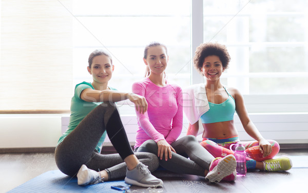women with bottles of water in gym Stock photo © dolgachov