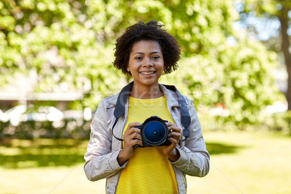 happy african woman with digital camera in park Stock photo © dolgachov