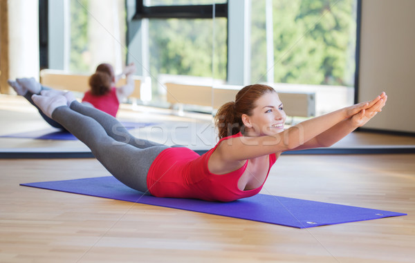 улыбающаяся женщина осуществлять спортзал фитнес спорт подготовки Сток-фото © dolgachov