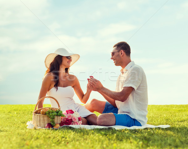 smiling couple with small red gift box on picnic Stock photo © dolgachov
