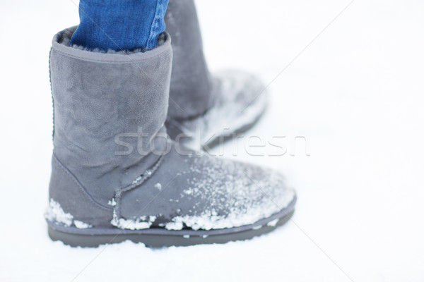 close up of woman legs wearing warm boots on snow Stock photo © dolgachov