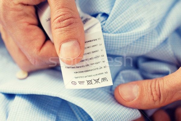 close up of male hands holding shirt and label Stock photo © dolgachov
