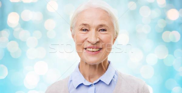 happy senior woman face over blue lights Stock photo © dolgachov