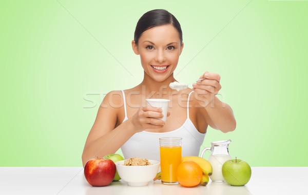 happy woman eating yogurt for breakfast Stock photo © dolgachov