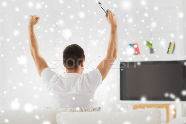 man watching tv and supporting team at home Stock photo © dolgachov