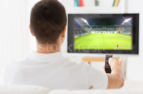 man watching football game on tv at home from back Stock photo © dolgachov