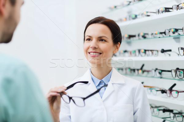 optician showing glasses to man at optics store Stock photo © dolgachov