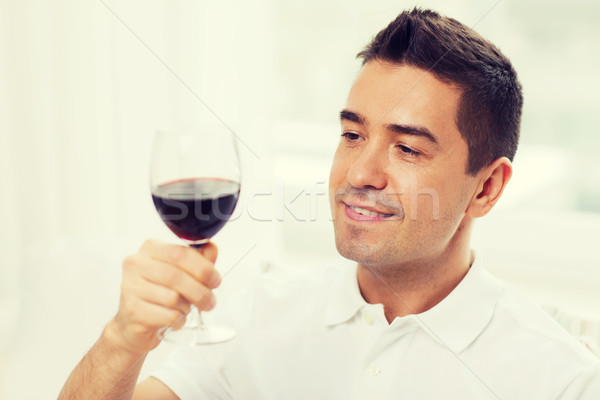 happy man drinking red wine from glass at home Stock photo © dolgachov