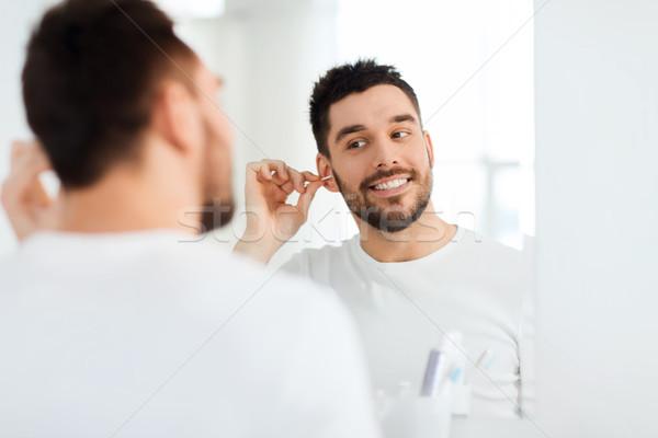 man cleaning ear with cotton swab at bathroom Stock photo © dolgachov