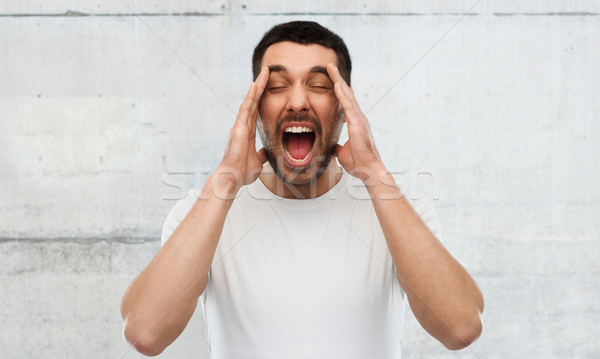 crazy shouting man in t-shirt over gray wall Stock photo © dolgachov