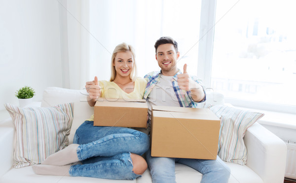 happy couple with boxes showing thumbs up at home Stock photo © dolgachov