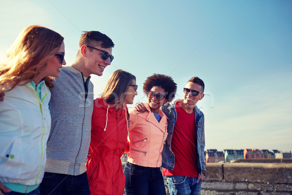 happy teenage friends walking along city street Stock photo © dolgachov