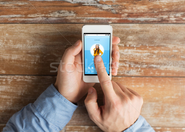 Stock photo: close up of male hands with smartphone on table