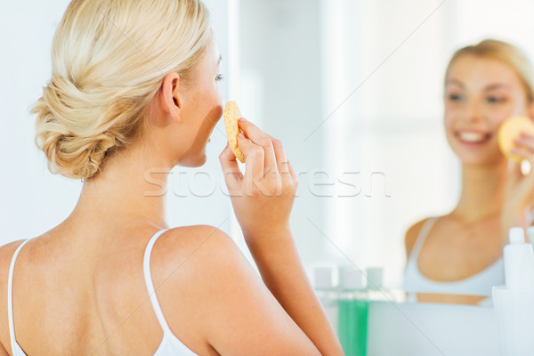 Stock photo: close up of woman washing face with sponge at home
