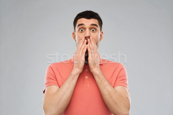 scared man in polo t-shirt over gray background Stock photo © dolgachov