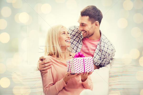 happy man giving woman present over holiday lights Stock photo © dolgachov