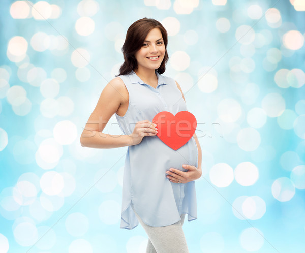 happy pregnant woman with red heart touching belly Stock photo © dolgachov