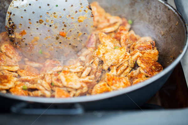 close up of meat in wok pan at street market Stock photo © dolgachov