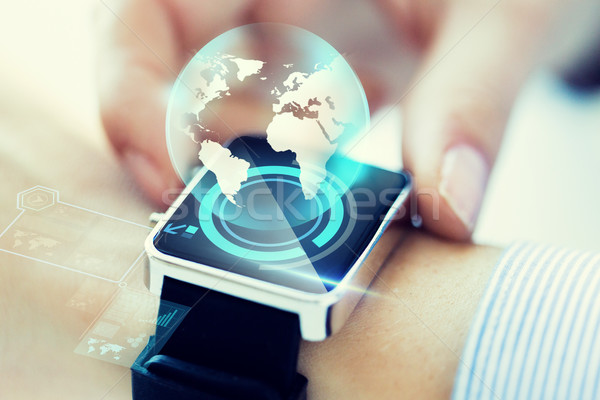 Stock photo: close up of hand with globe hologram on smartwatch