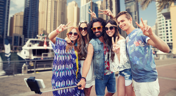 Stock photo: hippie friends with smartphone on selfie stick
