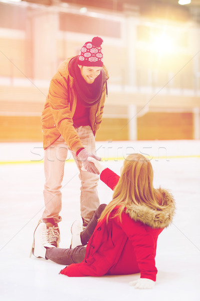 man helping women to rise up on skating rink Stock photo © dolgachov