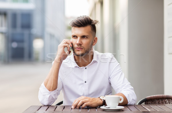 man with coffee calling on smartphone at city cafe Stock photo © dolgachov