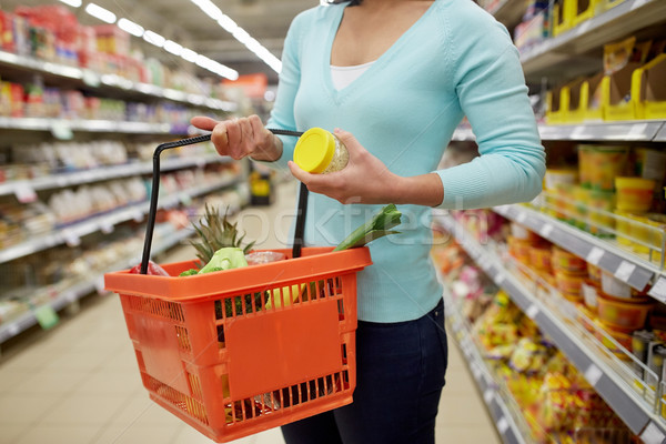 woman with food basket and jar at grocery store Stock photo © dolgachov
