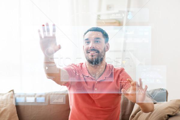 happy man touching virtual screen at home Stock photo © dolgachov