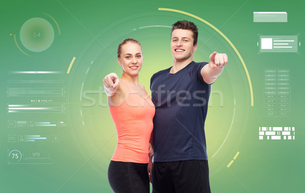 happy sportive man and woman pointing finger Stock photo © dolgachov
