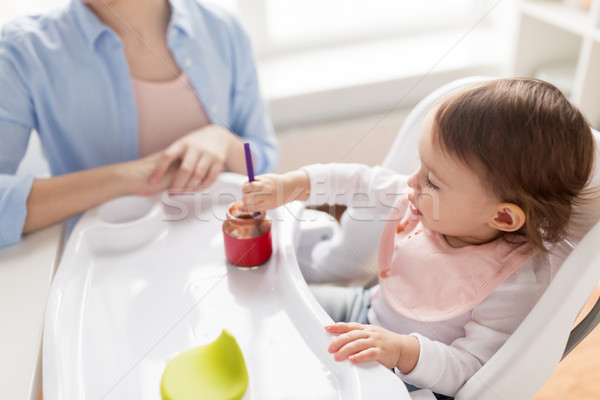 baby girl with spoon eating puree from jar at home Stock photo © dolgachov