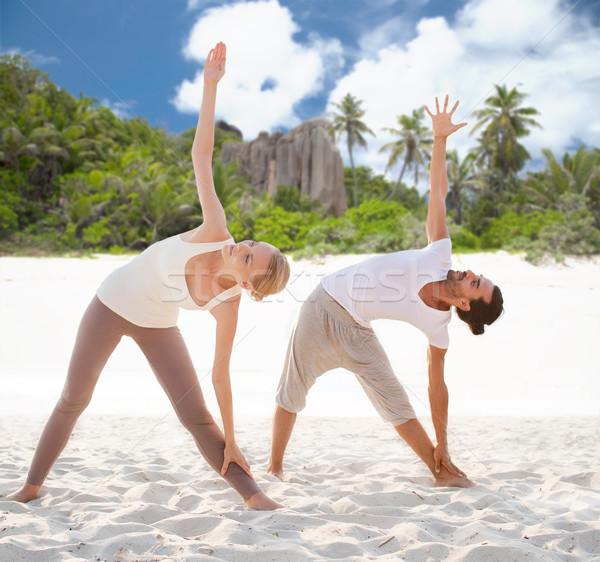 couple making yoga left triangle pose outdoors Stock photo © dolgachov