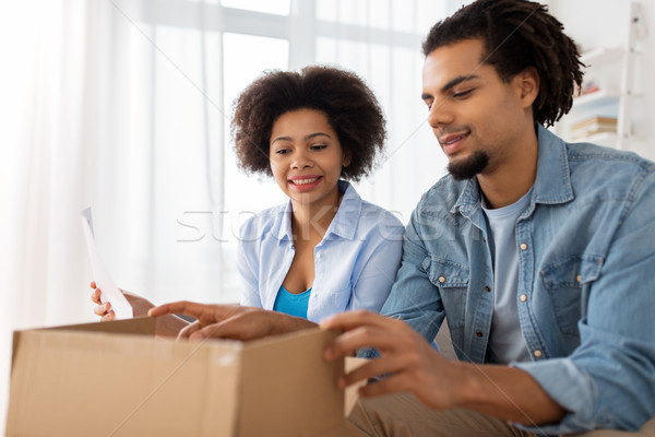 happy couple with parcel box and paper form home Stock photo © dolgachov