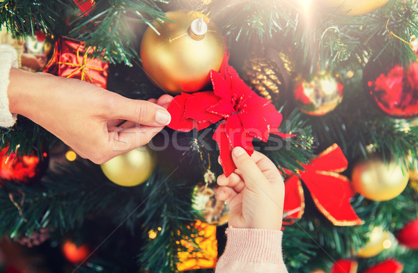 close up of family decorating christmas tree Stock photo © dolgachov