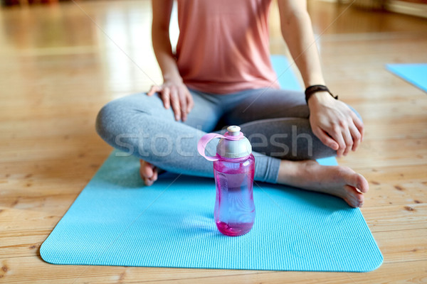 woman with water bottle resting on yoga mat in gym Stock photo © dolgachov