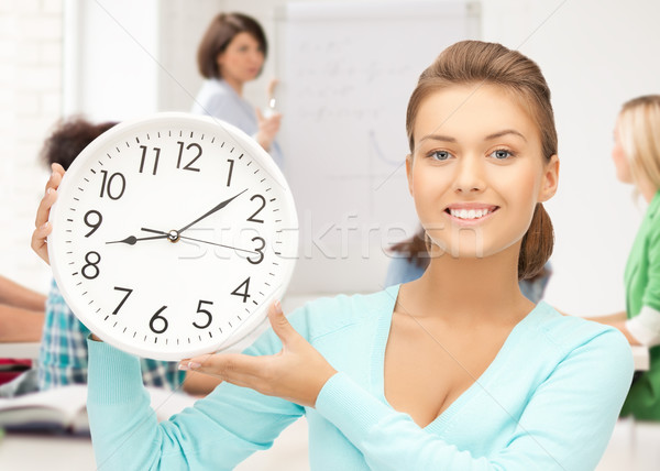 attractive student pointing at clock Stock photo © dolgachov