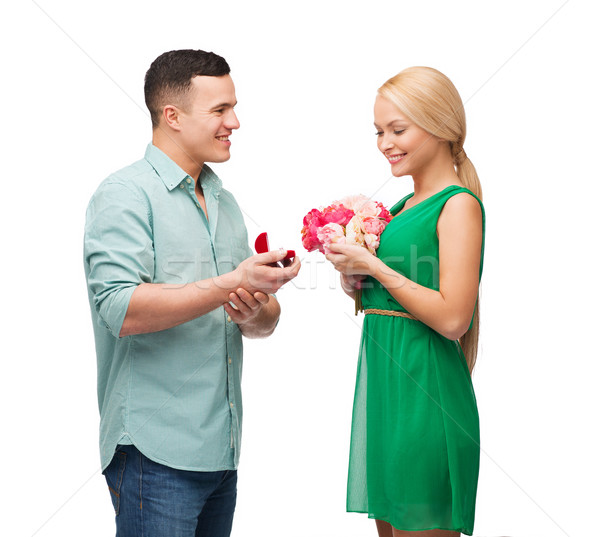 smiling couple with flower bouquet and ring Stock photo © dolgachov