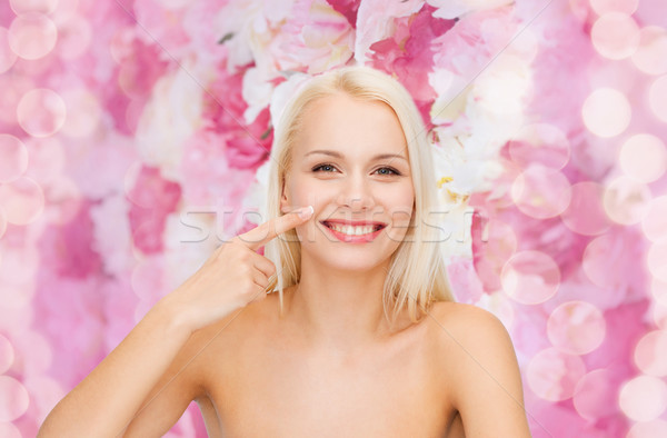 smiling young woman pointing to her nose Stock photo © dolgachov